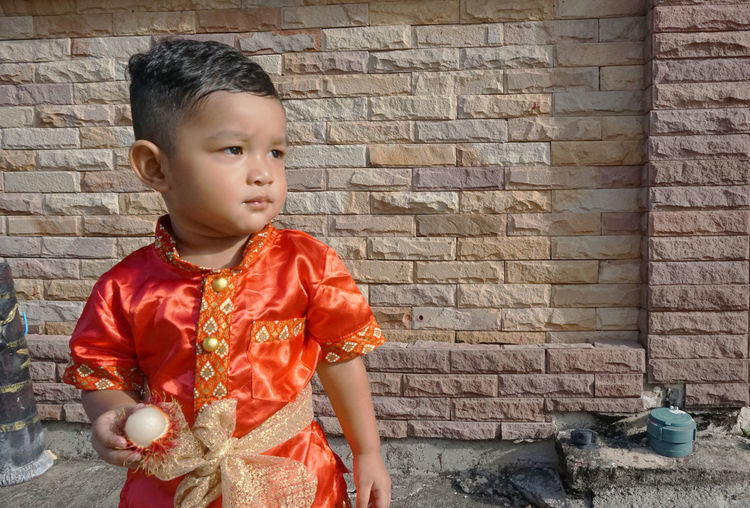 Cute baby boy holding fruit against brick wall