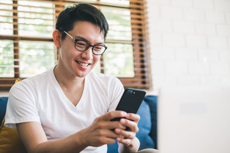Smiling young man using phone while sitting on sofa at home