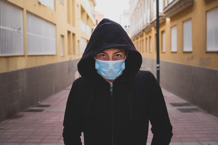 Portrait of teenage boy wearing hood standing against wall