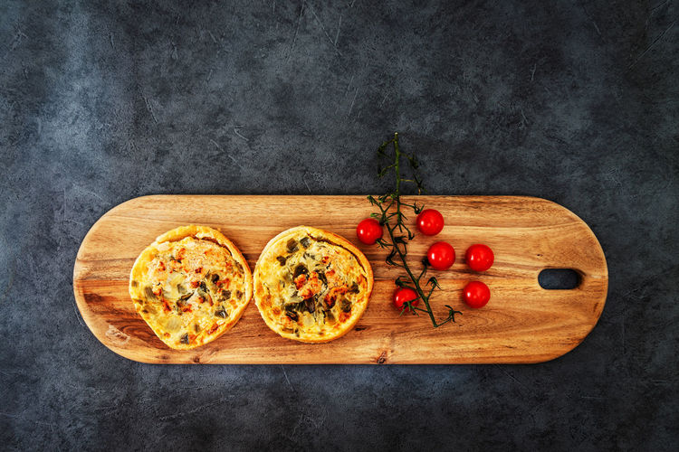 Directly above shot of savory pies and cherry tomatoes on wooden tray