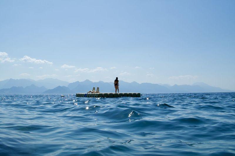 Man in sea against blue sky