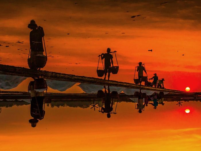 Workers on salt lake at sunset