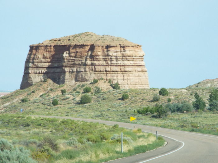 Road passing through rock formations against sky