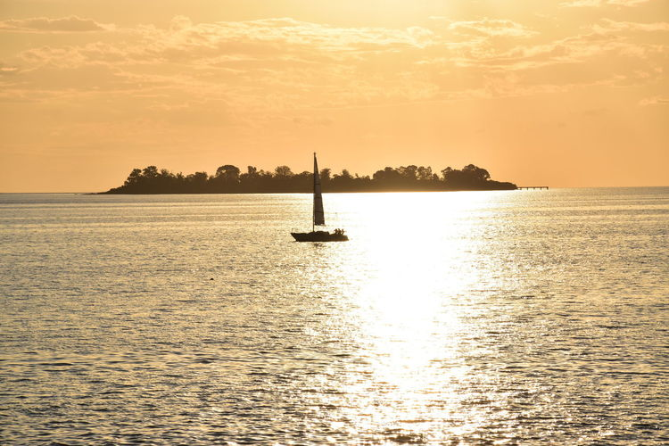 Sailboat Sailing In Sea Against Orange Sky