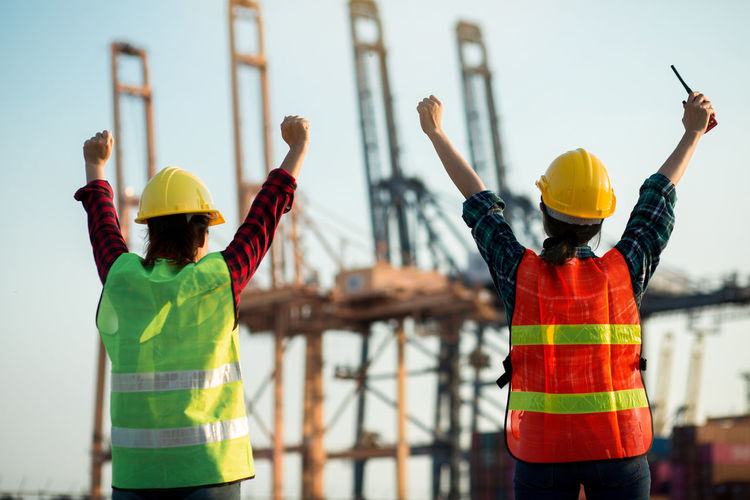 Rear view of people working at construction site