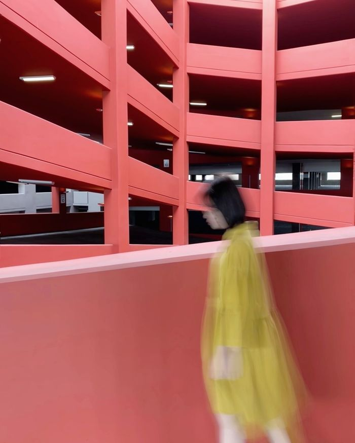 REAR VIEW OF WOMAN WITH RED UMBRELLA WALKING IN CORRIDOR