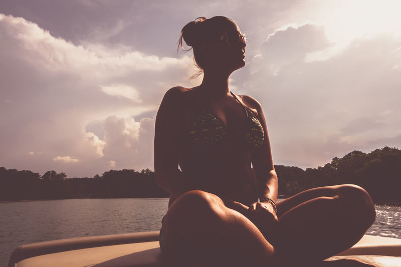 Woman sitting on boat in sea against sky during sunset