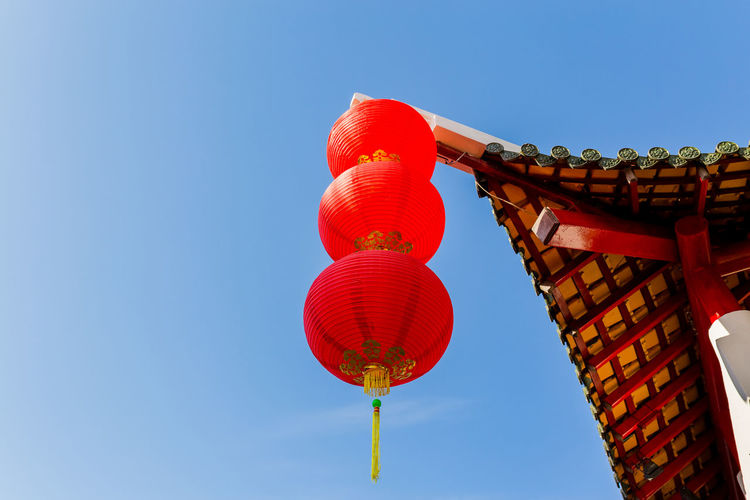 Low angle view of lanterns hanging against clear blue sky
