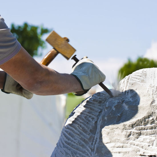 Young man at work with hammer and protective gloves to carving a stone block Artisan Skill  Carving Craftsperson Hammer Handmade Human Hand Marble Occupation One Person Outdoors Protective Gloves Sculpting Sculptor Sculpture Stone Block Stone Material Worker