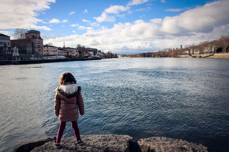 Girl Water Rear View Cloud - Sky Real People Sky One Person Lifestyles Leisure Activity Full Length Nature Women Architecture Standing Built Structure Rock Casual Clothing Day Outdoors Looking At View Saone City Child Cityscape River Loooking Standing