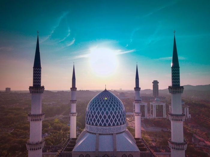 High angle view of mosque against sunny sky