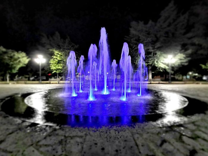 Illuminated fountain by lake against sky at night