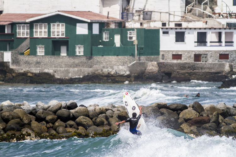 Rear View Of Man Surfboarding On Groyne In Sea