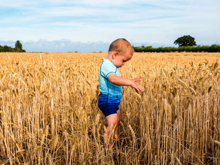 Side view of cute boy standing on wheat field against sky