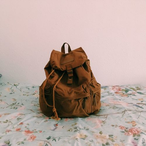 Brown Backpack On Bed By Wall In Room
