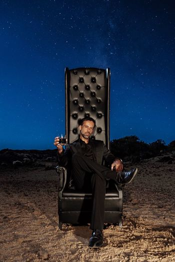 Portrait Of Mature Man Holding Drink While Sitting On Chair Against Sky At Night