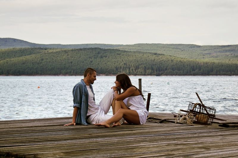 Romantic Couple Sitting On Pier By Lake Against Sky