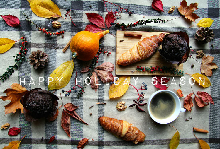Happy Holiday Season Greeting Card With Autumn Themed Picnic On The Background Food And Drink Food Freshness Indoors  High Angle View Directly Above No People Cutting Board Autumn Mood Autumn Autumn colors Muffin Chocolate Croissant Black Coffee Picnic Blanket Pinecone Hazelnut Autumn Leaves Leaves Happy Holidays! Holiday Season Greeting Card  Card Design Note