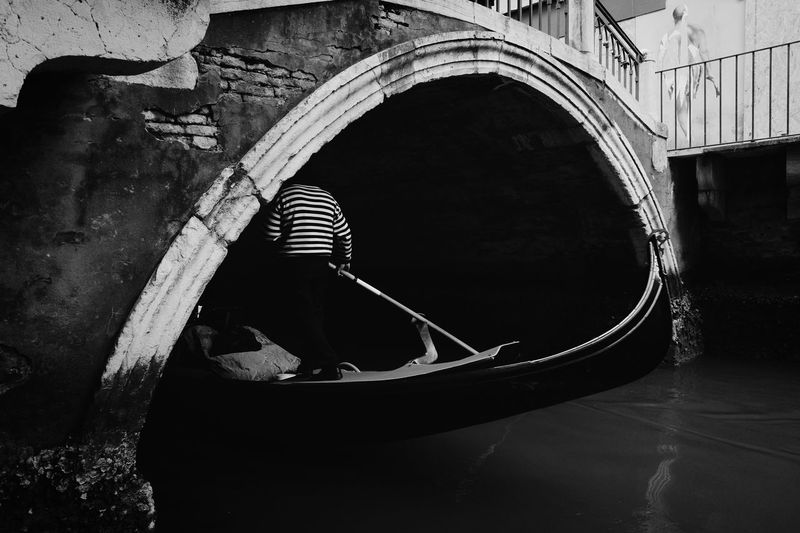 Reflection of man in boat on canal