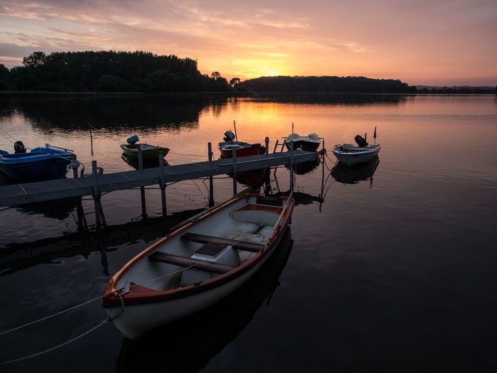View Of Boats Moored At Dock During Sunset