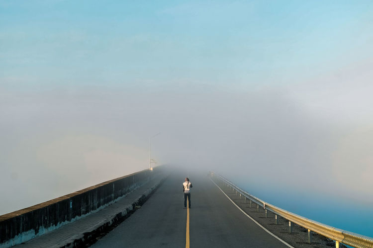 Rear view of man standing on bridge against sky during foggy weather