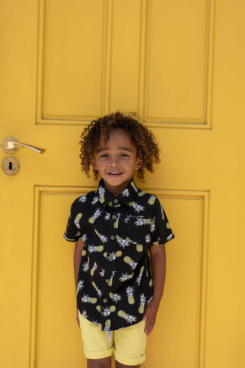 Yellow Smiling Childhood Child Portrait Happiness One Person Looking At Camera Standing Front View Indoors  Emotion Three Quarter Length Door Yellow Curly Hair Cheerful Casual Clothing Entrance Innocence Hairstyle