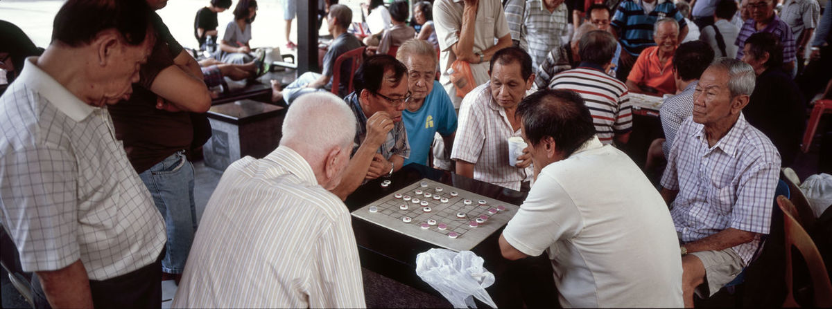 Two men play xiangqi while others look on in an outdoor recreation spot in Singapore's Chinatown district. Image © Brian Kerrigan 2016 Chinatown Chinatown, Singapore Chinese Chess City Life Crowd Full Frame Large Group Of People Men Outdoors Singapore Xiangqi