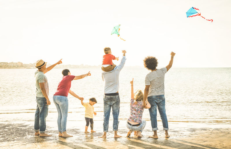 Family flying kites at sea shore against clear sky