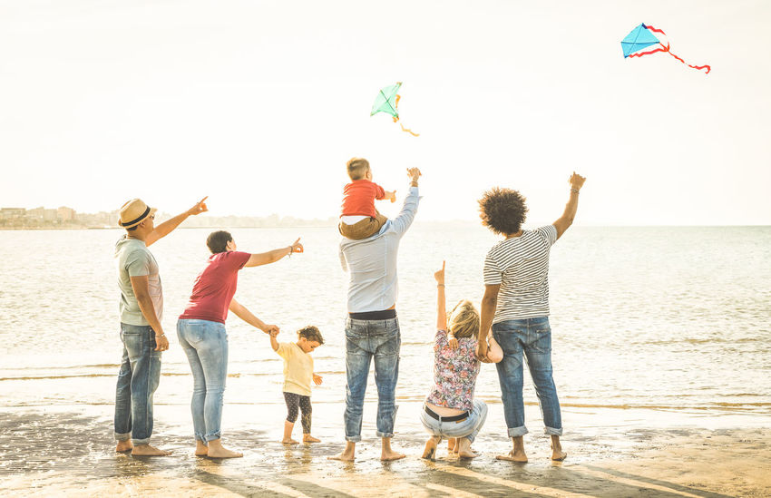 Happy families group with parents and children playing with kite at beach vacation - Summer joy happiness concept with mixed race people having fun together at sunset - Warm vintage backlight filter Multiracial  Multiethnic Family Families Multi Racial Mixed Race Outdoors Beach Fun Having Fun Travel Summer Happy Children Kids Parents Together Kite Playing Sea Joy Education Time Enjoying Life
