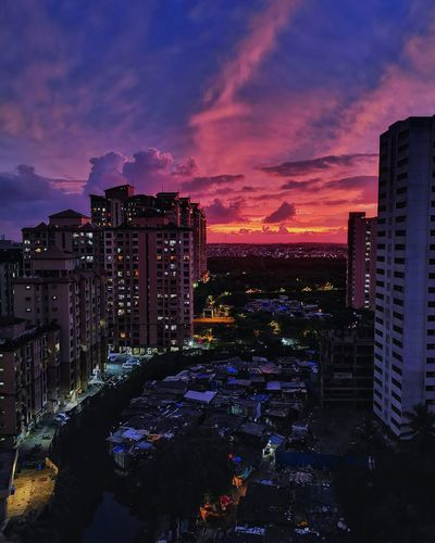 High angle view of illuminated buildings against dramatic sky