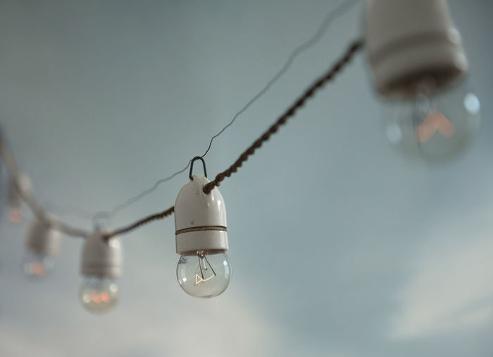 Low angle view of light bulb hanging against sky