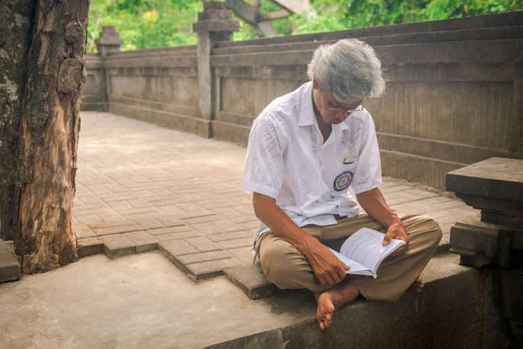 Reading alone Indonesian The Portraitist - 2018 EyeEm Awards Activity Architecture Blairwaldorf Book Casual Clothing Cultural Day Front View Full Length Gray Hair Holding Leisure Activity Lifestyles Nature One Person Outdoors Publication Reading Real People Religion Senior Adult Sitting Style