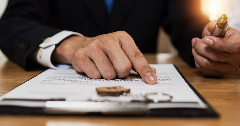 Midsection of man holding paper on table