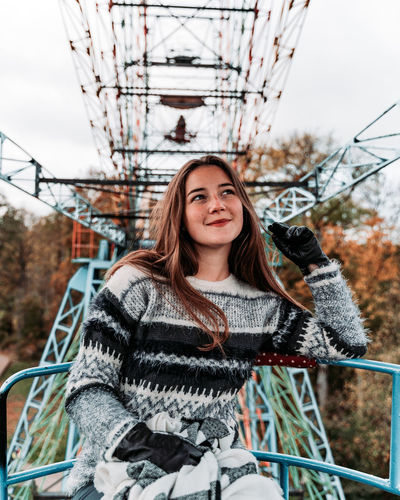 Smiling young woman sitting on ferris wheel