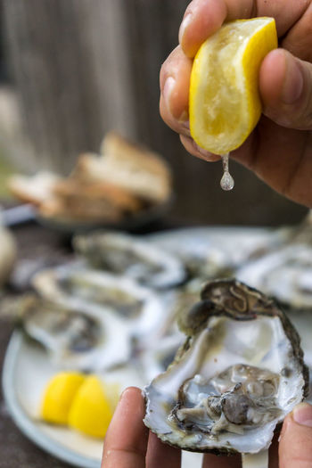 Cropped Hand Squeezing Lemon On Oyster
