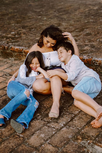 High angle view of smiling mother with son and daughter sitting on land