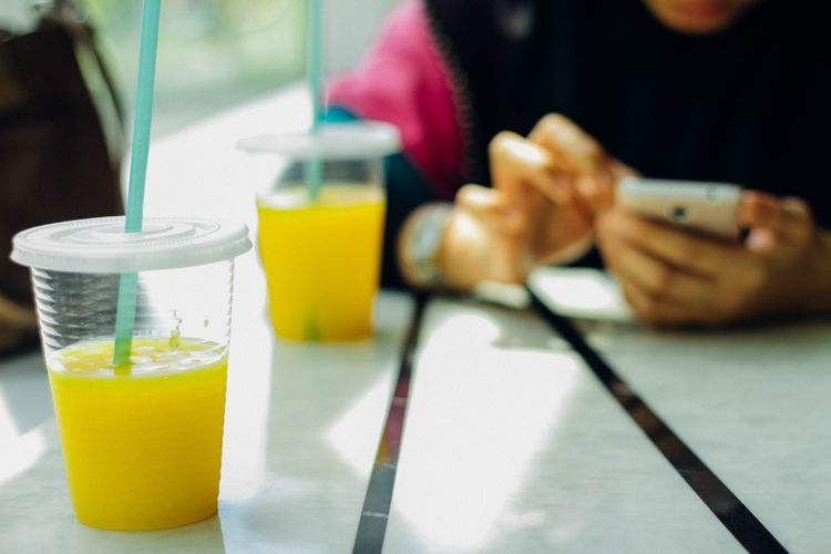 Midsection of girl using mobile phone by mango juices at restaurant table