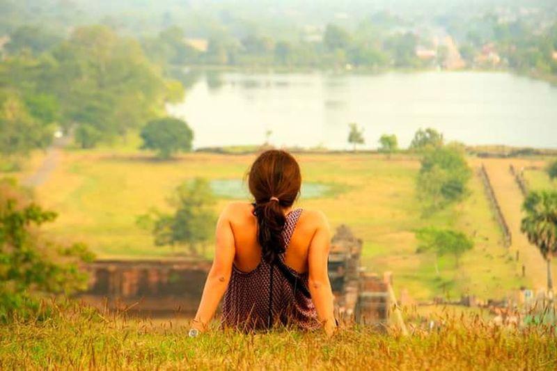 Rear view of woman sitting in field