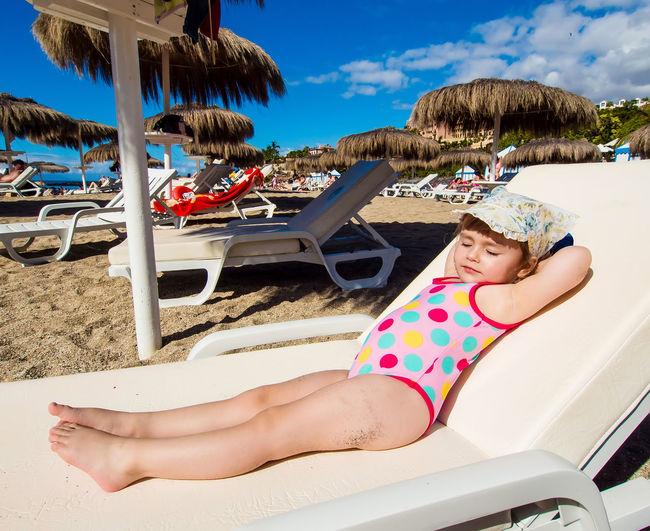 Girl Lying On Lounge Chair At Beach