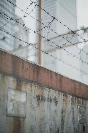 Architecture No People Built Structure Wall - Building Feature Focus On Foreground Metal Day Safety Building Building Exterior Fence Outdoors Protection Security Boundary Wall Close-up Selective Focus Damaged Barrier Concrete Streetphotography Street Wall