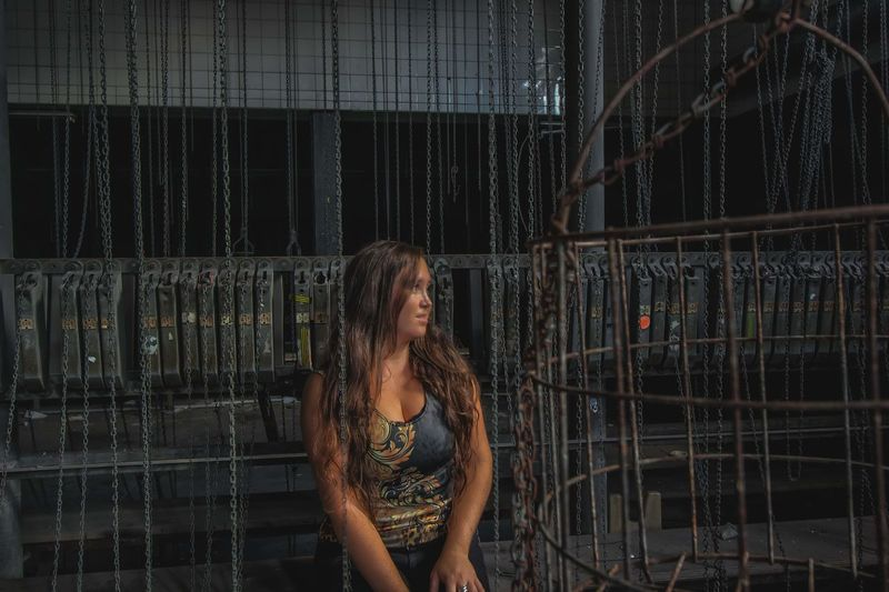 Smiling woman looking away while standing by metal