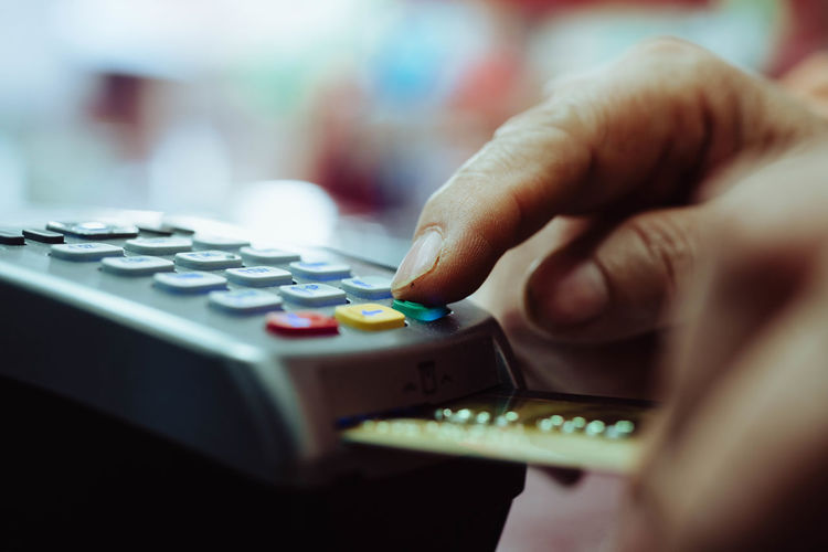 Cropped hand of man using credit card for payment in store