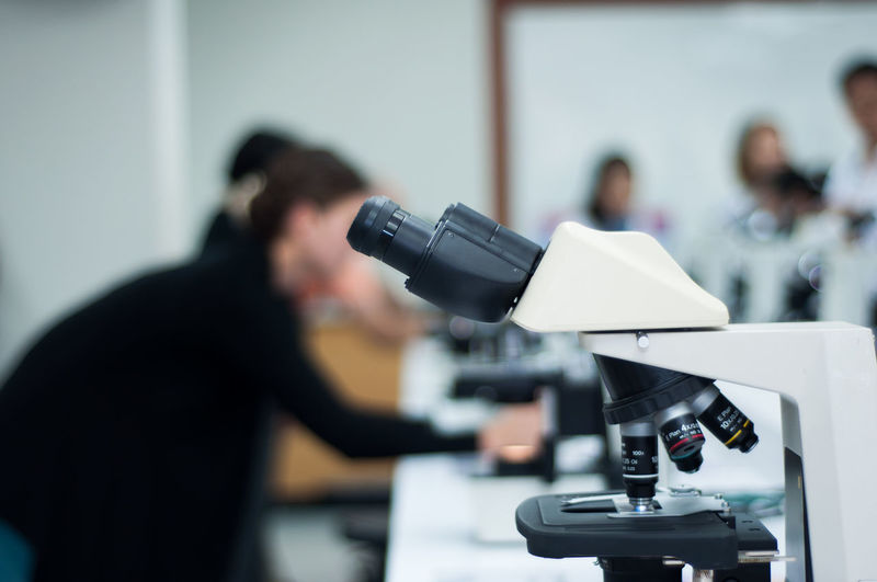 Close-up of microscope with scientists in background at laboratory