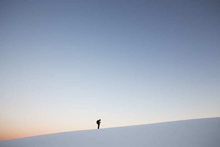 Man standing on snowcapped mountain against clear sky at sunset