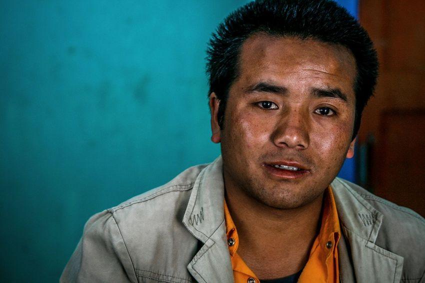Disco Lama Portraits Of EyeEm Zimithang Arunachal Pradesh Warm Clothing Tawang Disco Lama Monk  Lama Portrait Portrait Photography Portrait Headshot Men Looking At Camera Colored Background Mid Adult Close-up Head And Shoulders Blue Background Mug Shot