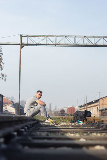 Side View Of Man Sitting On Railroad Track In City