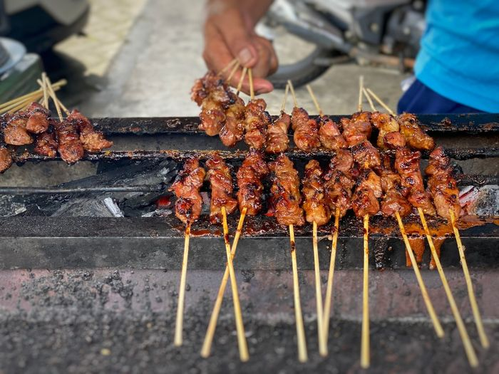 Person holding meat on barbecue grill