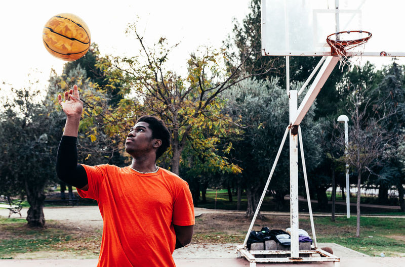 Young man spinning ball on finger at basketball court
