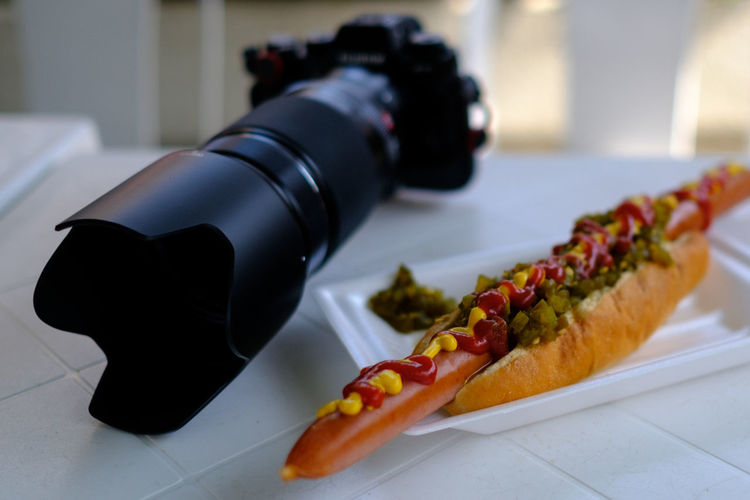 Close-up of hot dog and camera on table
