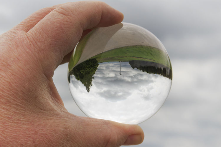 Cropped hand holding crystal ball against cloudy sky